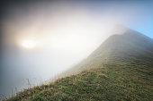mountain peak in fog at sunrise