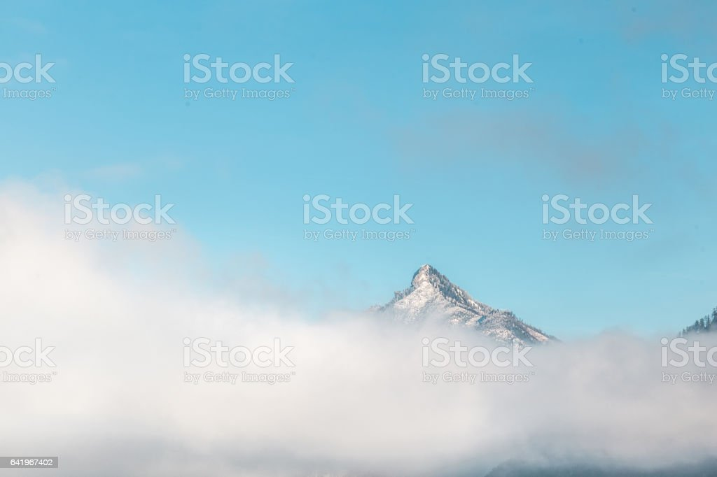 Mountain peak with snow over clouds stock photo