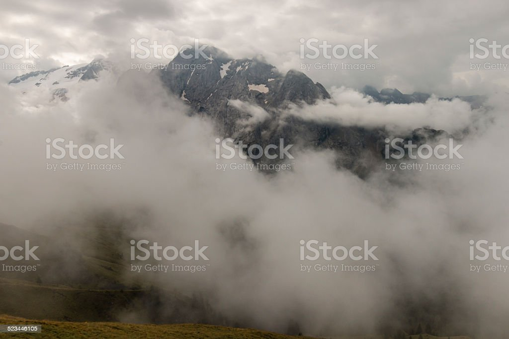 mountain range in Dolomites obscured by clouds stock photo