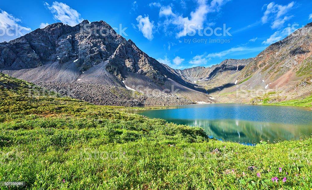 Mountain range near the lake and alpine meadow stock photo