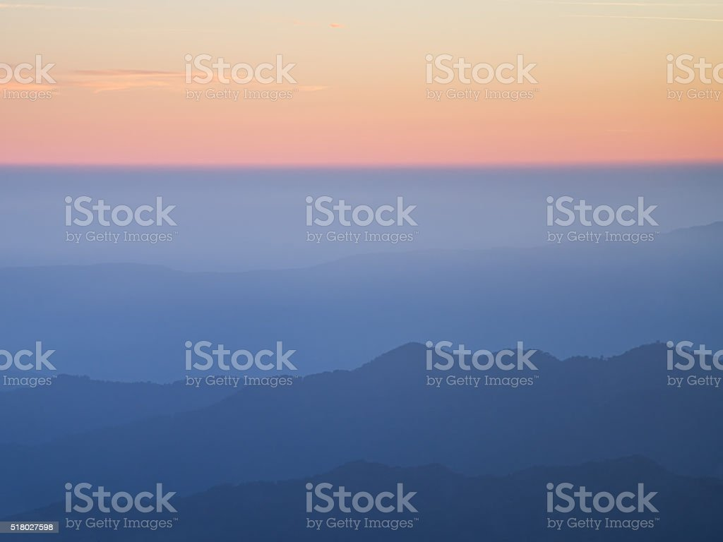 Mountain range with layer mist on evening glow background stock photo