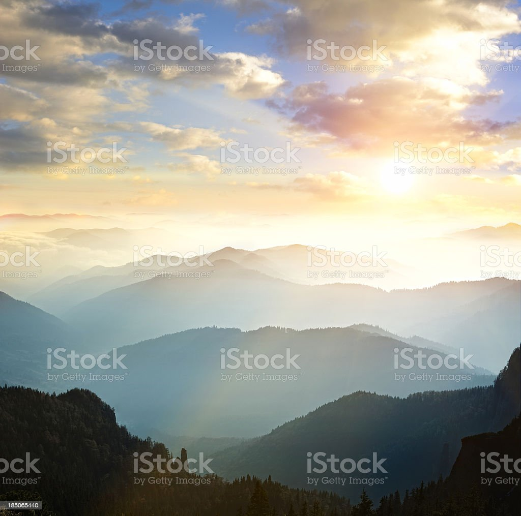 Mountain range with sun setting in background stock photo