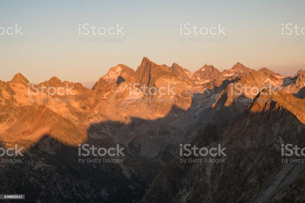 mountain ranges in sunlight at sunset or sunrise stock photo