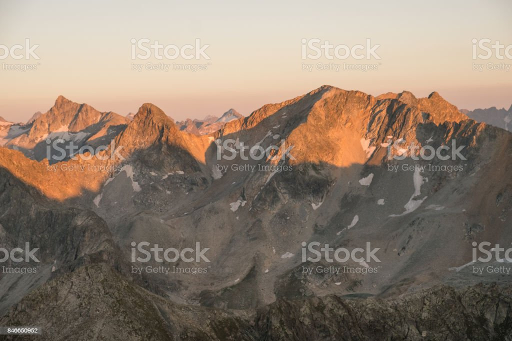 mountain ranges with snow in the sunlight at dusk or dawn in the Caucasus stock photo