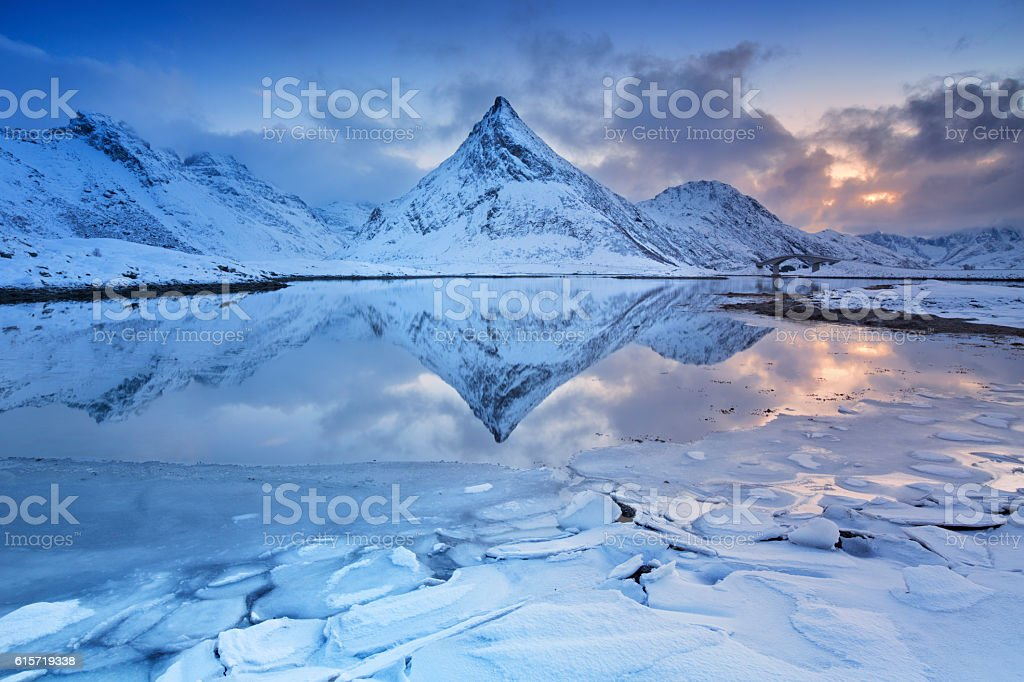Mountain reflected in a fjord in Norway in winter stock photo