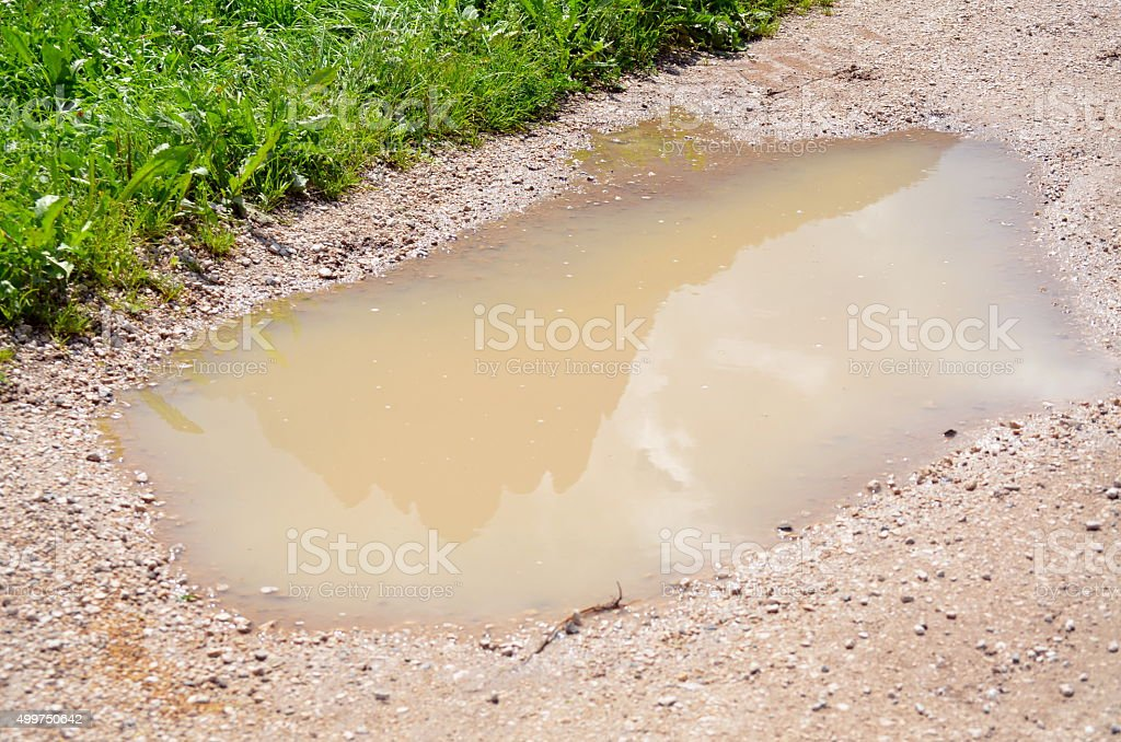 mountain reflected in a puddle of mud stock photo