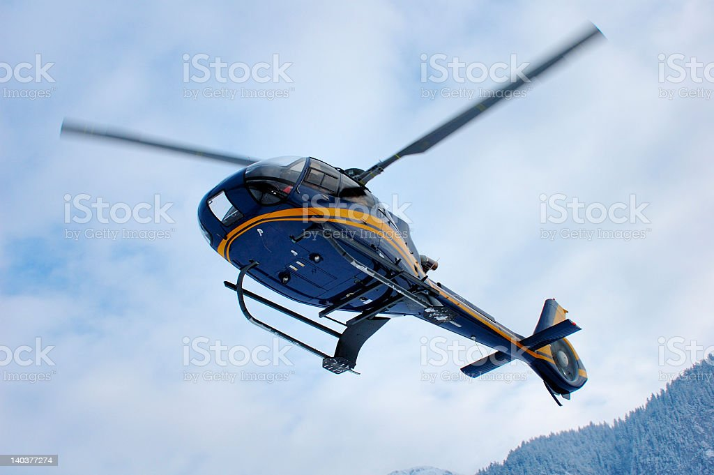 A mountain rescue helicopter flying against a cloudy sky stock photo