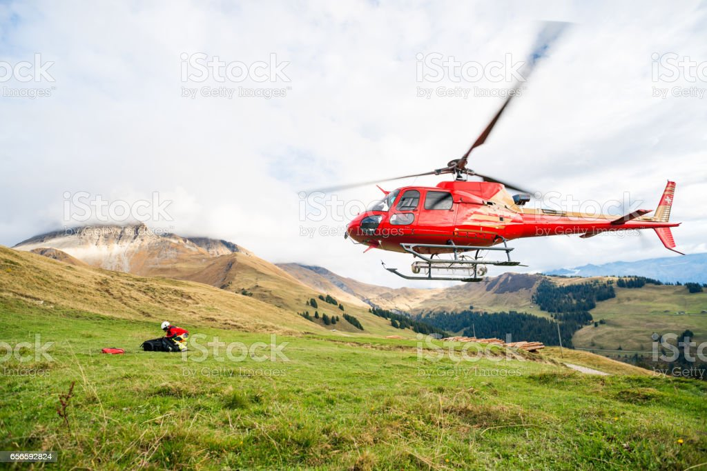 Mountain Rescue Helicopter Takes Off From Mountain Side stock photo
