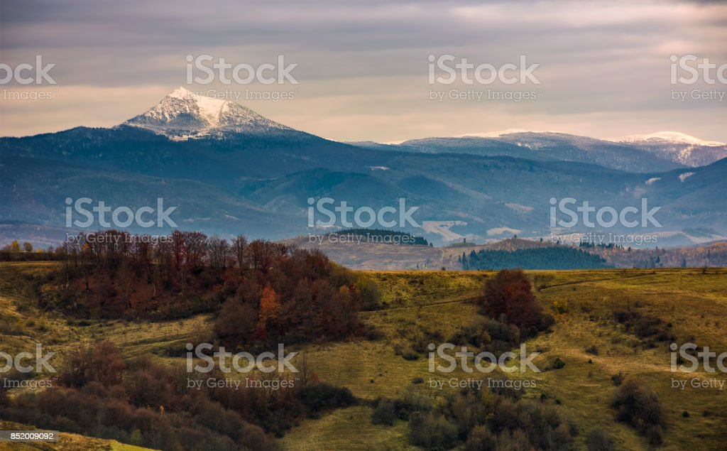 mountain ridge with snowy peak on gloomy day stock photo