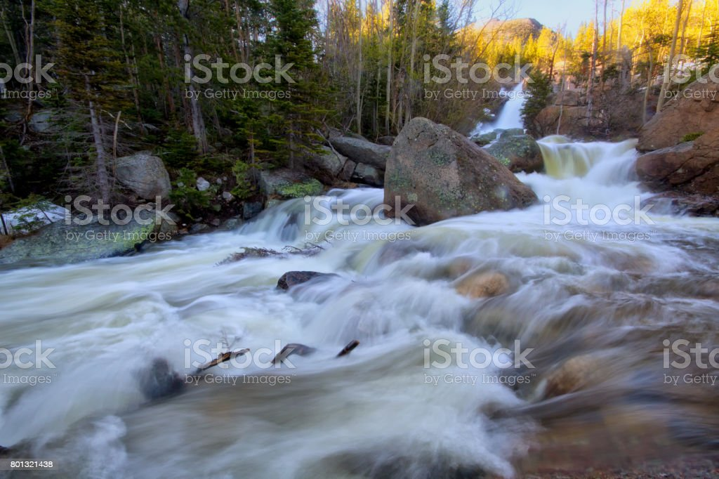 Mountain river flowing with a waterfall in the background in the spring season stock photo
