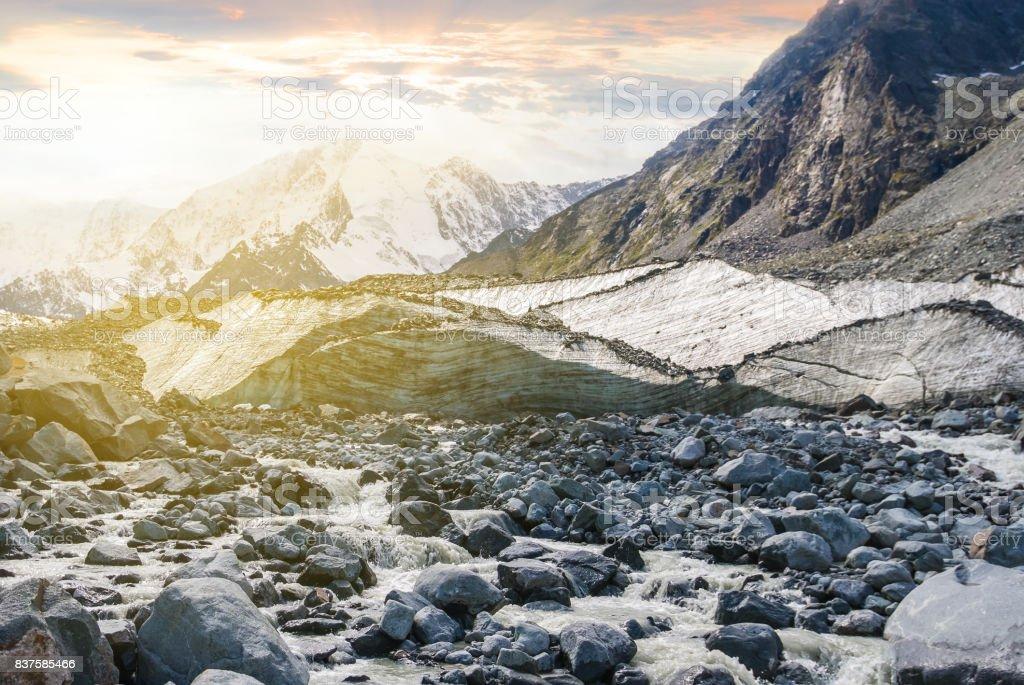 mountain river rushing through a mountain glacier stock photo