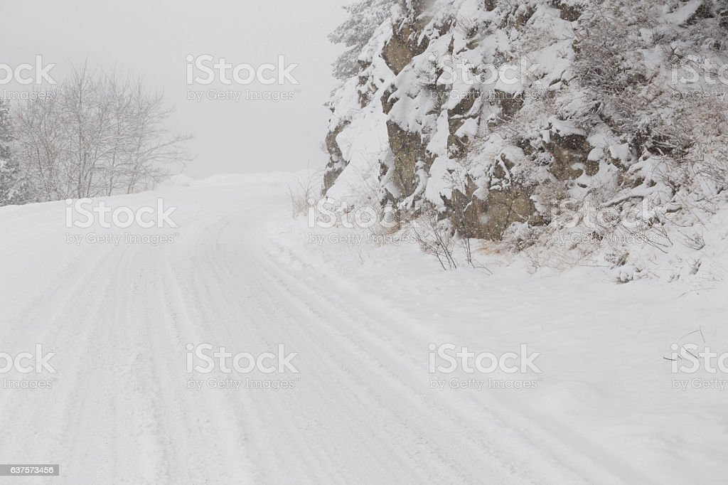 Mountain road covered in blizzard snow stock photo