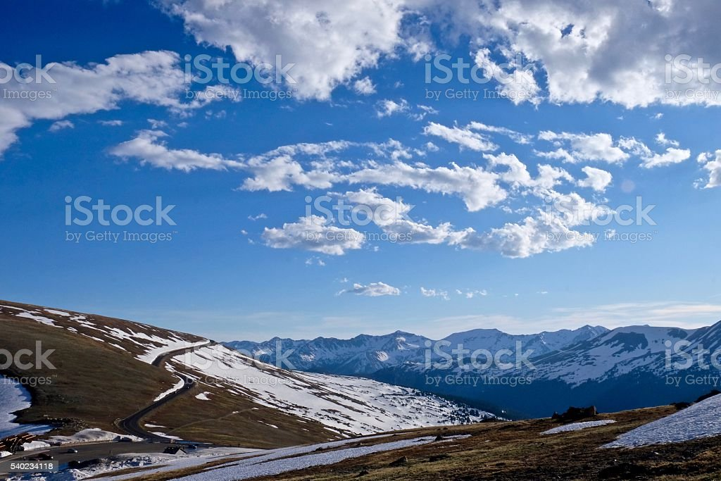 Mountain Road through Snow under Sky with Clouds. stock photo
