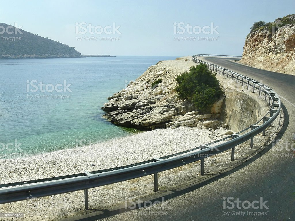 Mountain road with a beach right next to it royalty-free stock photo