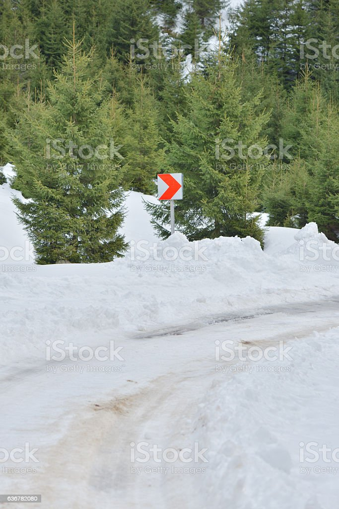 Mountain snow covered road between green fir trees, curve sign stock photo