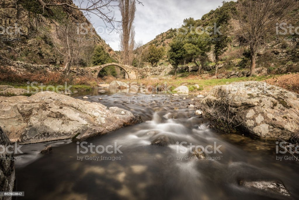 Mountain stream cascading under an ancient Genoese bridge in Corsica stock photo