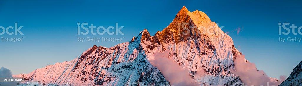 Mountain sunset golden light illuminating sacred Himalaya peak Machapuchare Nepal stock photo