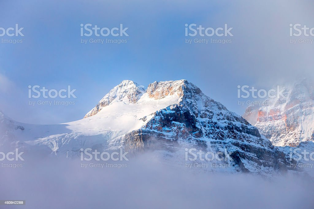Mountain surrounded in the heavy fog stock photo