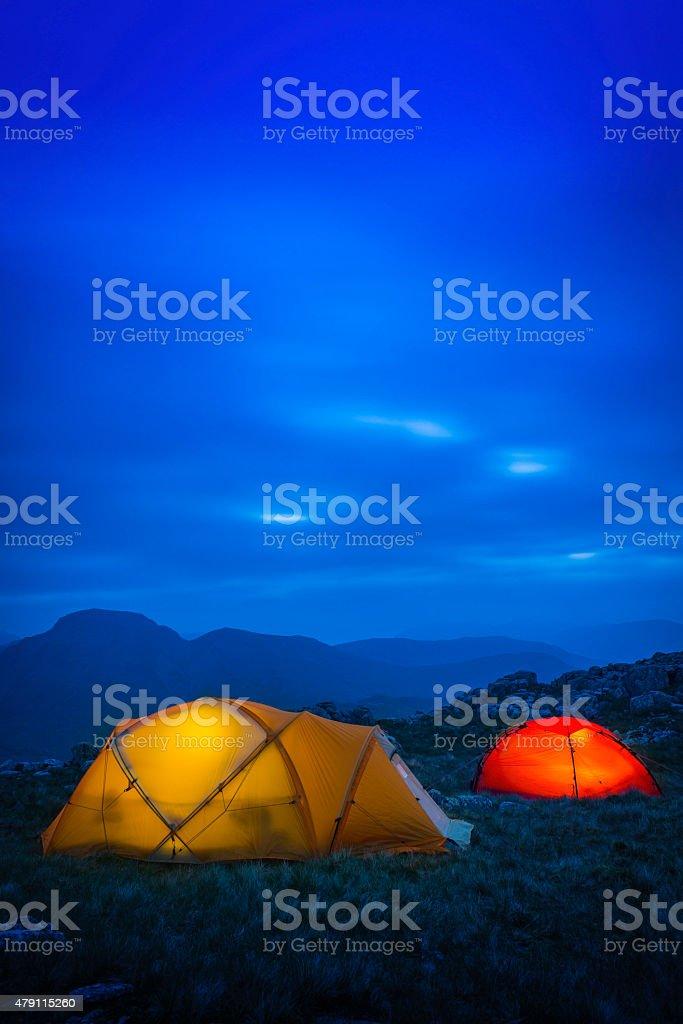 Vibrant mountain tents warmly illuminated against the blue dusk sky,...