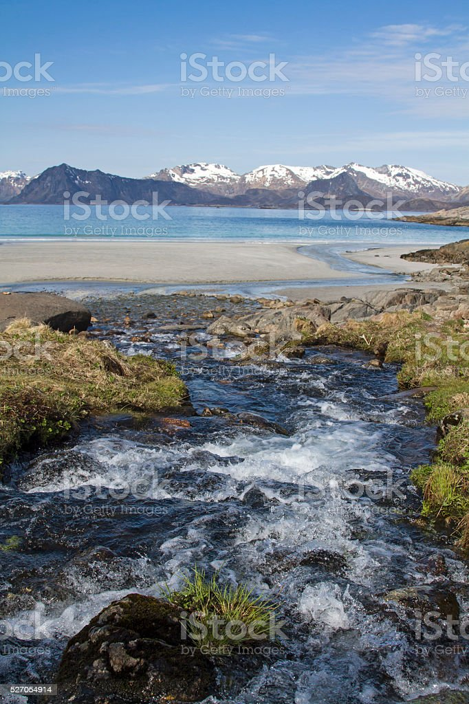 Mountain torrent on the sandy beach stock photo