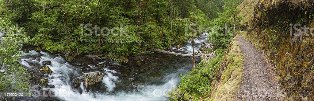 Mountain trail running along river ravine cascade panorama stock photo