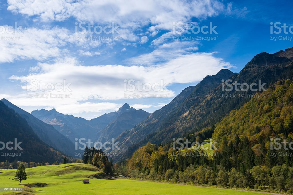Mountain valley with mountains and meadow stock photo