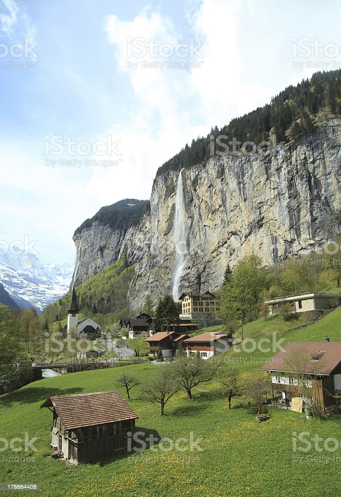 mountain village with church and waterfall, Alps, Switzerland . royalty-free stock photo