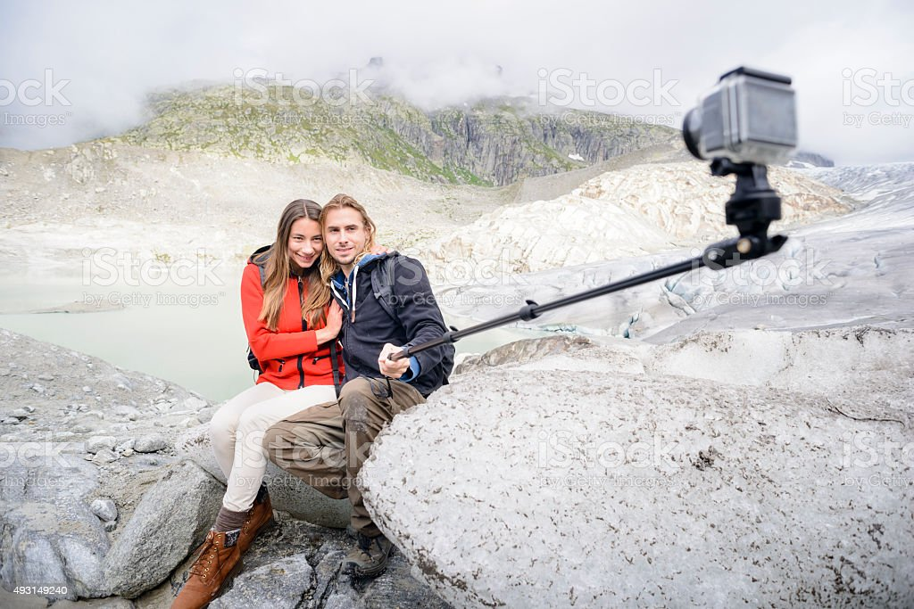 Mountain Walking Couple Taking Selfie with Video Action Camera stock photo