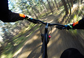 Mountainbiker going through turns in the forrest (POV)
