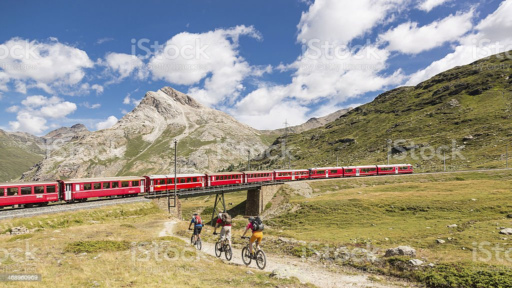 Mountainbiker meets Bernina Express, Switzerland stock photo