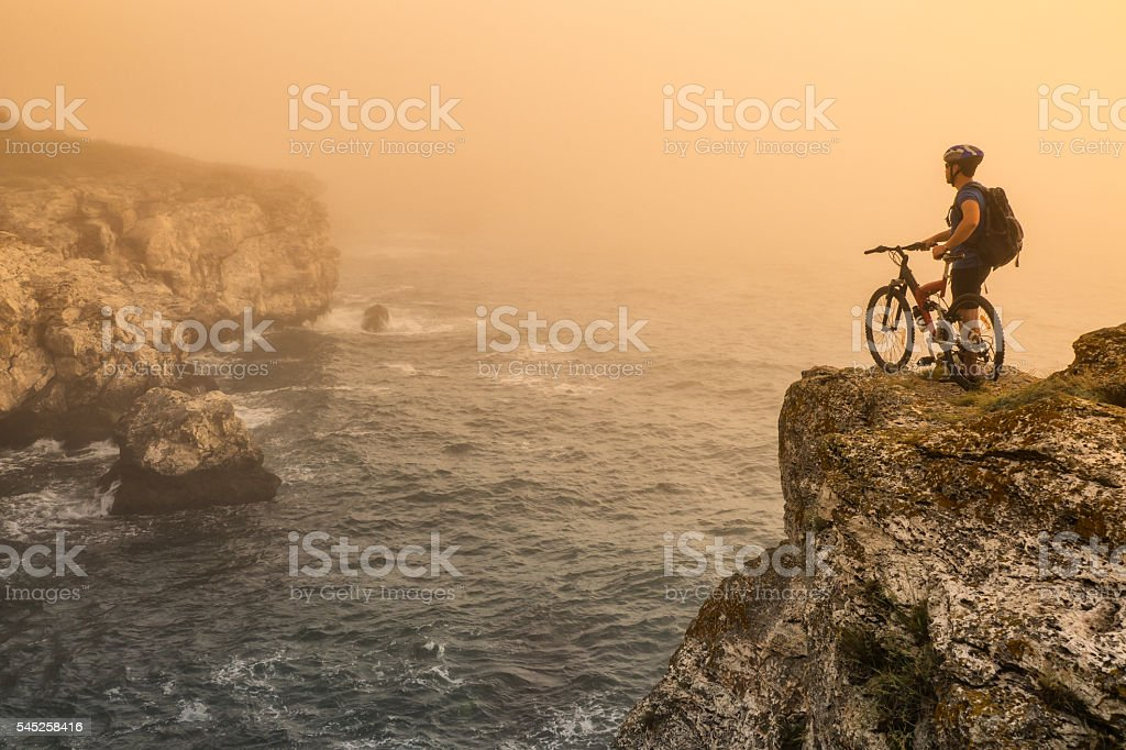 Mountainbiker standing on top of the rock stock photo