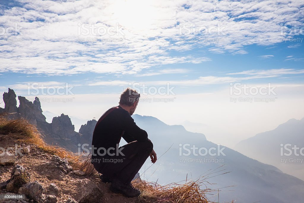 Mountaineer admires the mountain landscape stock photo