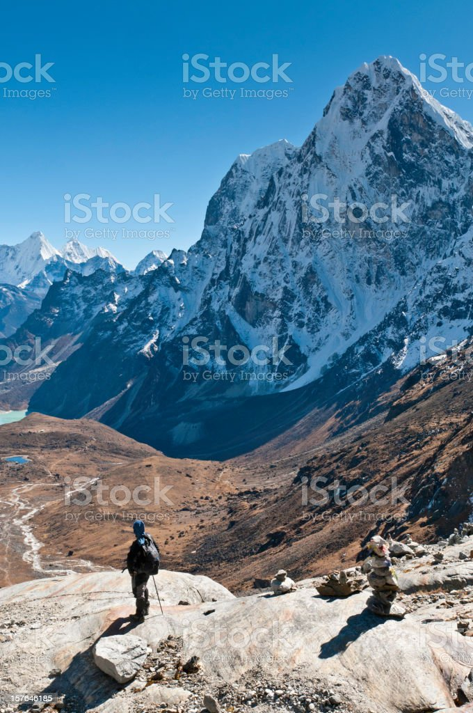 Mountaineer contemplating dramatic mountain view snow capped peaks Himalayas Nepal royalty-free stock photo