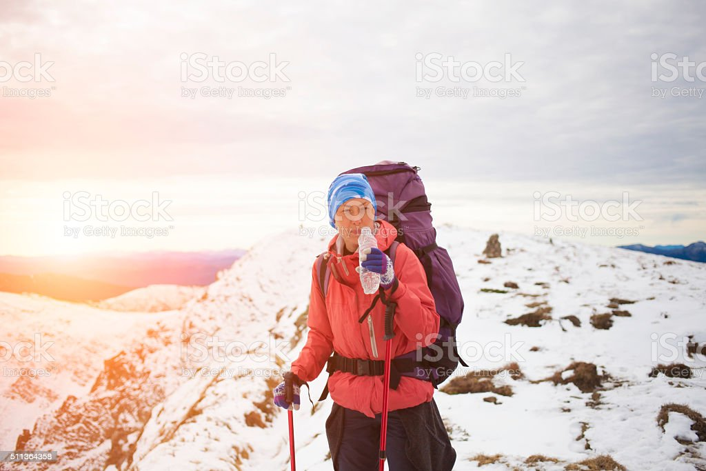 Mountaineer drinks water on top of the mountain. stock photo