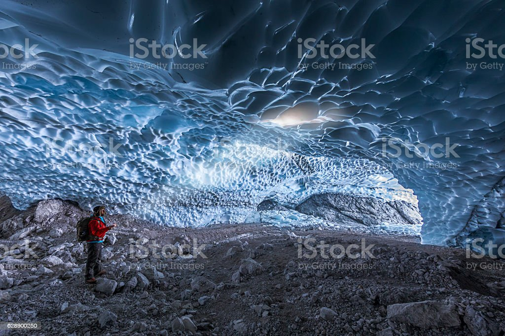 Mountaineer lit with torch in ice cave  Berchtesgaden National Park stock photo