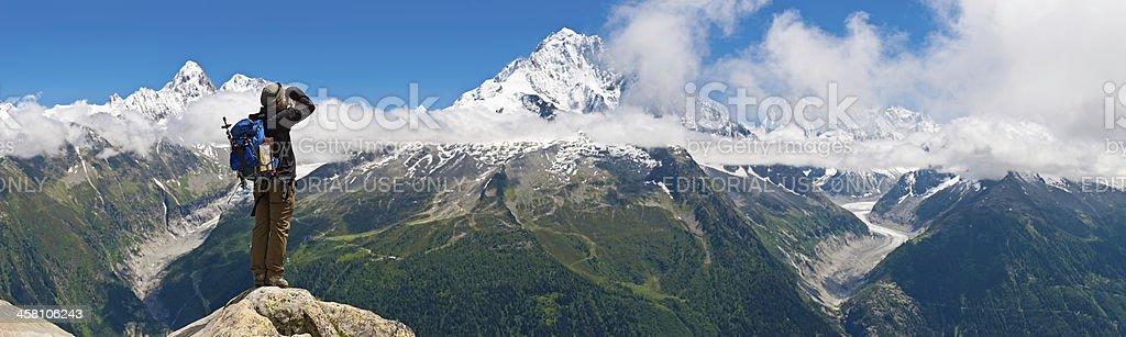 Mountaineer photographing dramatic Alpine peak panorama royalty-free stock photo