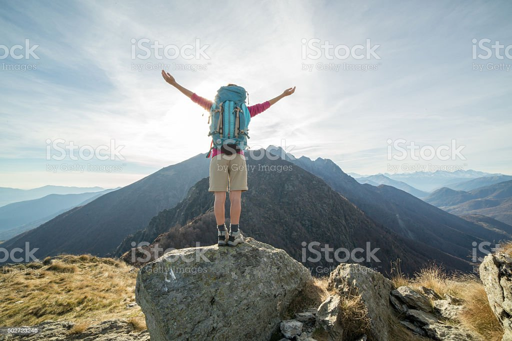 Young woman hiking reaches the mountain top, outstretches arms for...