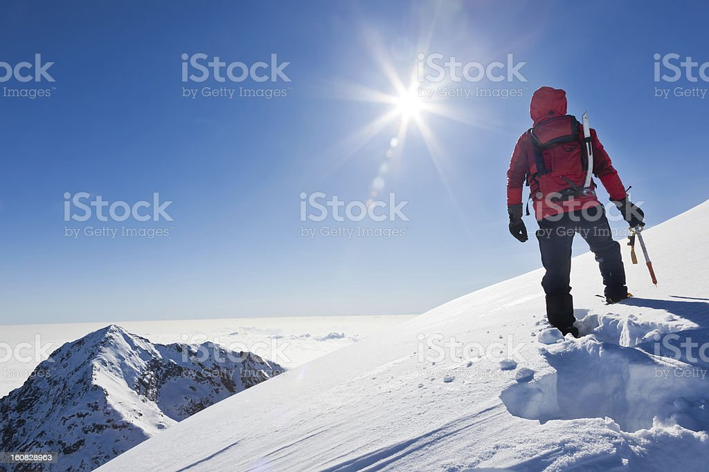 Mountaineer reaches the top of a snowy mountain royalty-free stock photo