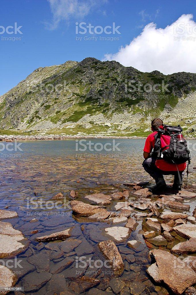 Mountaineer resting near a mountain lake royalty-free stock photo