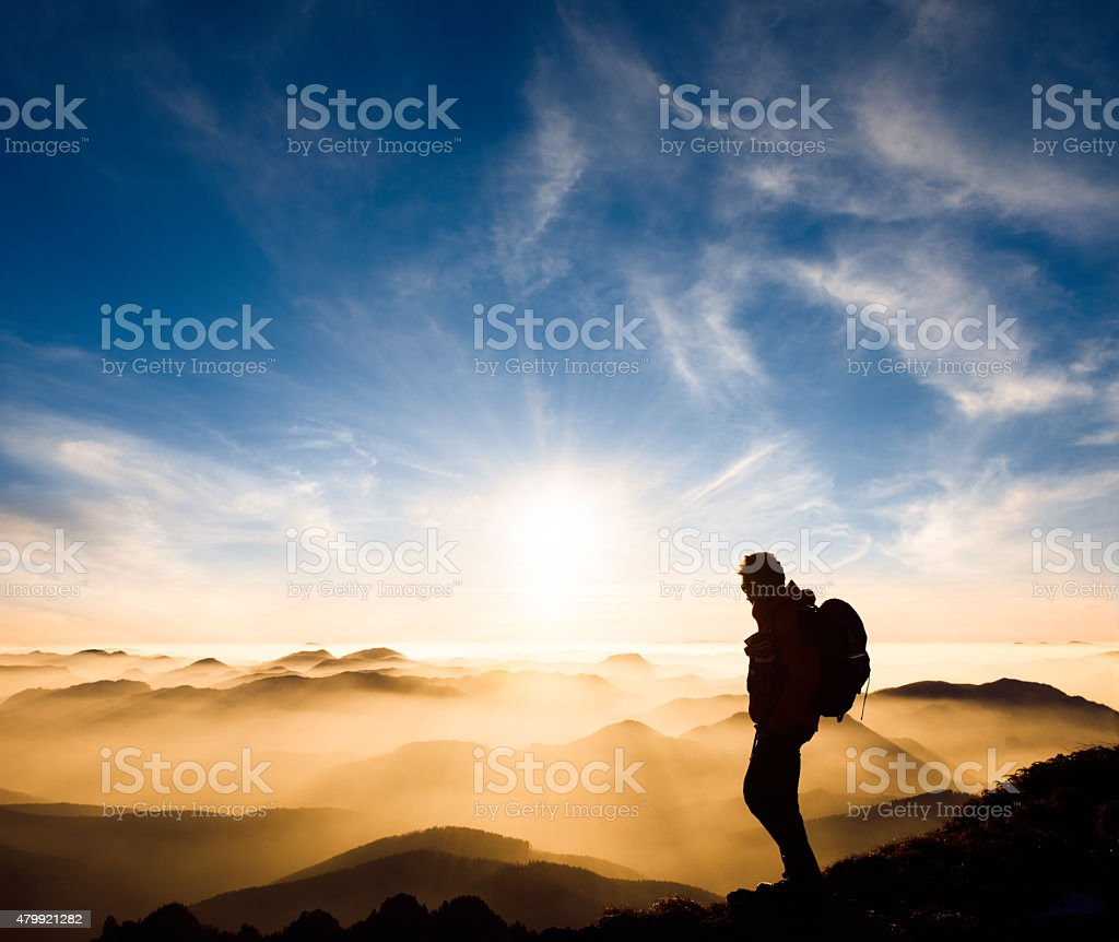 Mountaineer silhouette standing on top of the mountains stock photo
