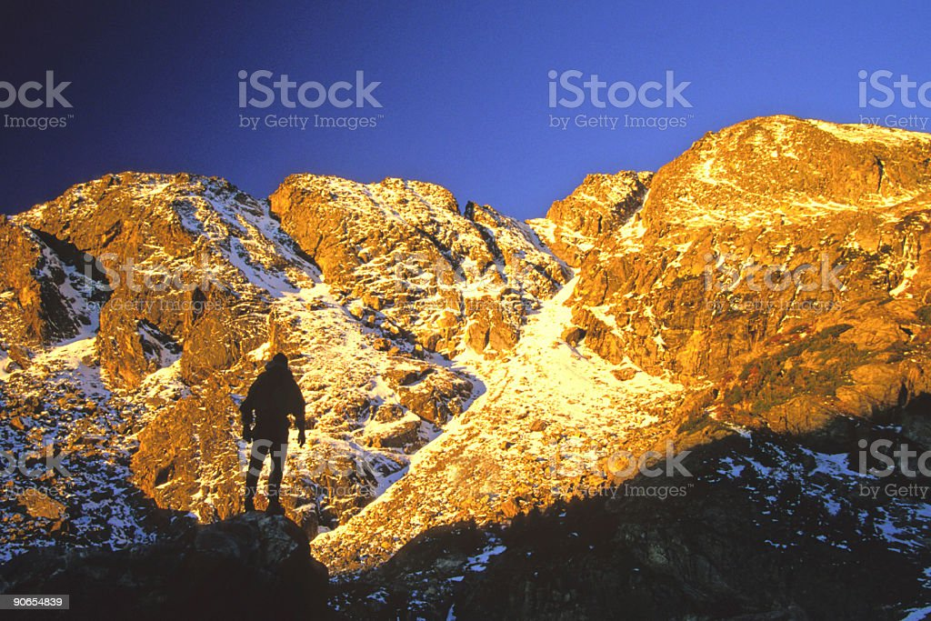 mountaineer silhouetted against sunset mountains royalty-free stock photo
