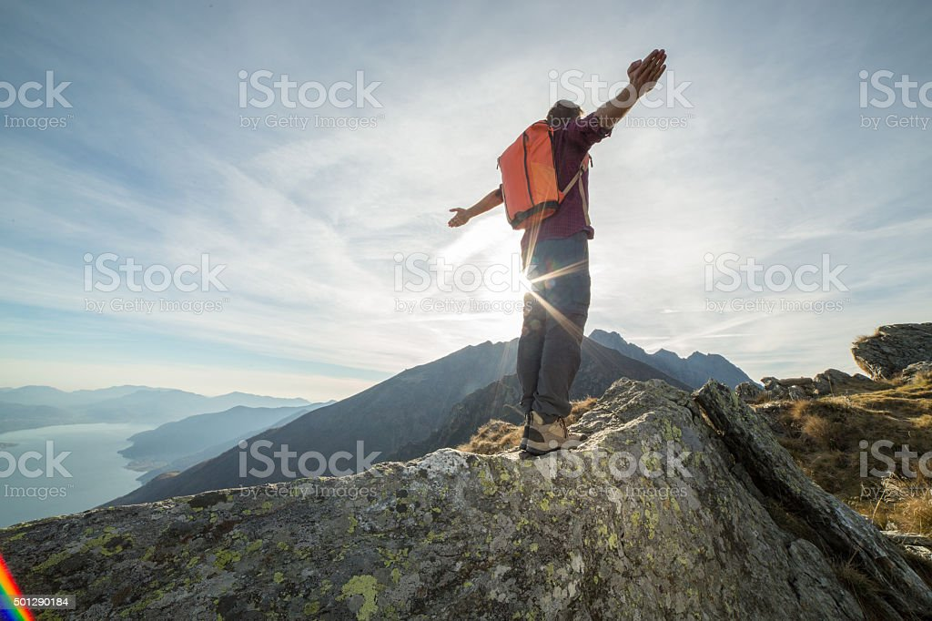 Mountaineer stands arms outstretched on mountain top stock photo