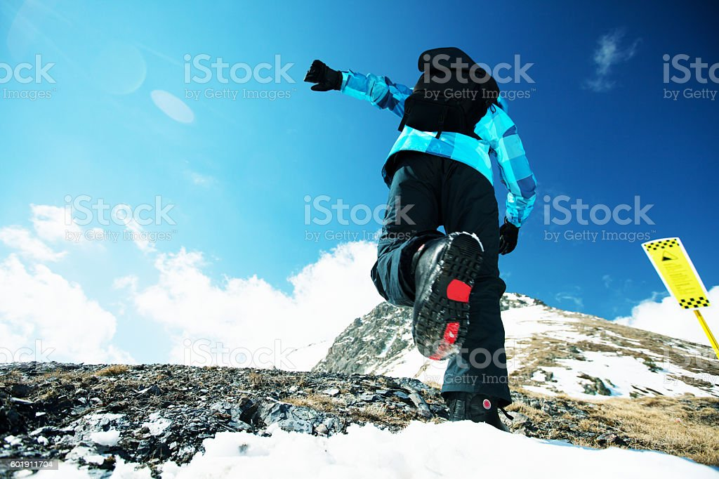 Mountaineer walking up along a snowy ridge stock photo