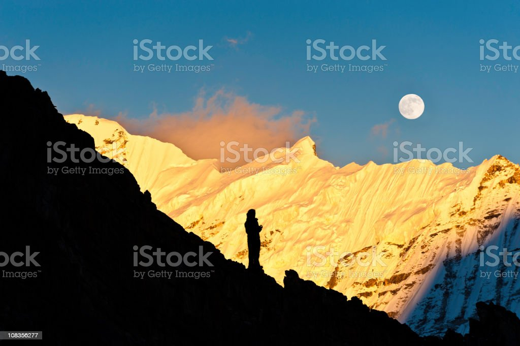 Mountaineer watching moon rise over golden sunset snow summit Himalayas stock photo