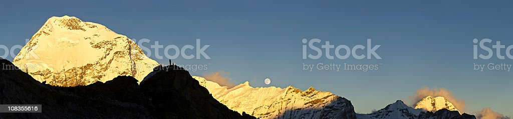 Mountaineer watching sunset full moon rising golden mountain summit panorama stock photo