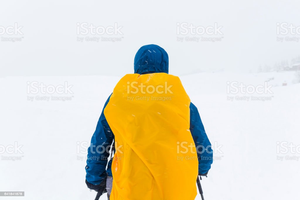 Mountaineer with covered backpack stock photo