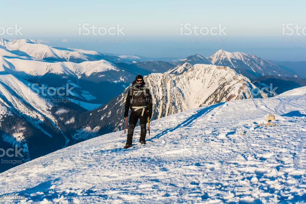 Mountaineer with ice axes and backpack in mountains in winter. stock photo