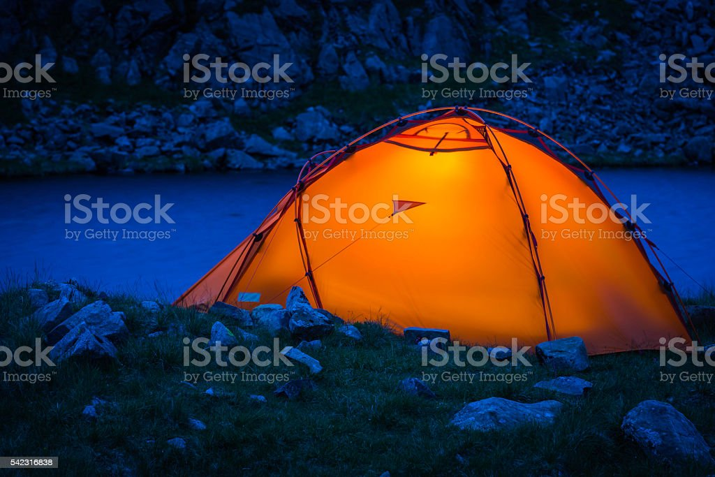 Mountaineering tent illuminated in blue dusk mountain lake wilderness camp stock photo