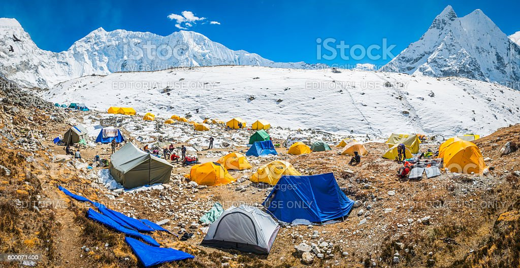 Mountaineers at base camp tents snowy Himalaya mountains wilderness Nepal stock photo