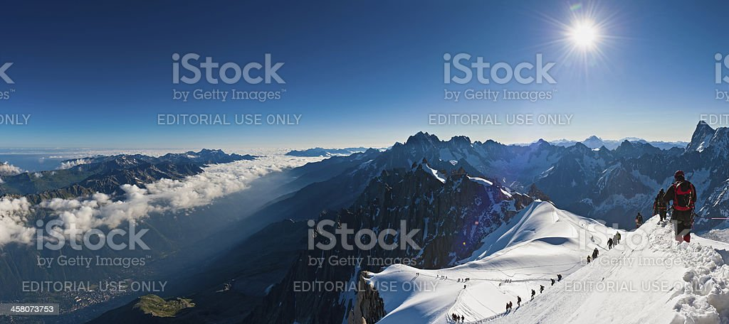 Mountaineers climbing above the clouds Alps panorama stock photo